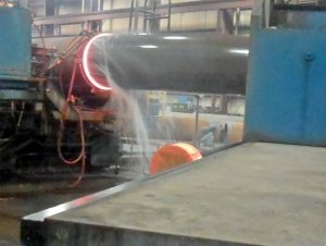Bending a large pipe at the CBI plant. The glowing band is where the pipe is heated by electric current induction, then bent by the machine at right. Water is sprayed on the already bent portion to prevent over bending.