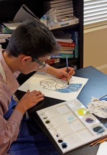 Sebastian painting Greek armor using Prussian blue and cobalt blue with carbon black pigment he made.