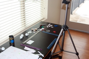 Set up for the stop-motion animation activity. You will need a solid tripod, a black-topped table with good lighting, and rulers to mark the edges of the stage area (camera field of view).