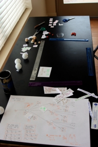 Animation stage (marked with rulers). Since the camera couldn't point straight down, the stage is a trapezoid. On the large sheet of paper is our storyboard/plan.