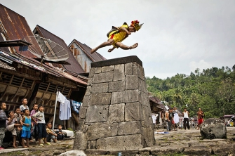 A villager wearing traditional costume jumps over a stone